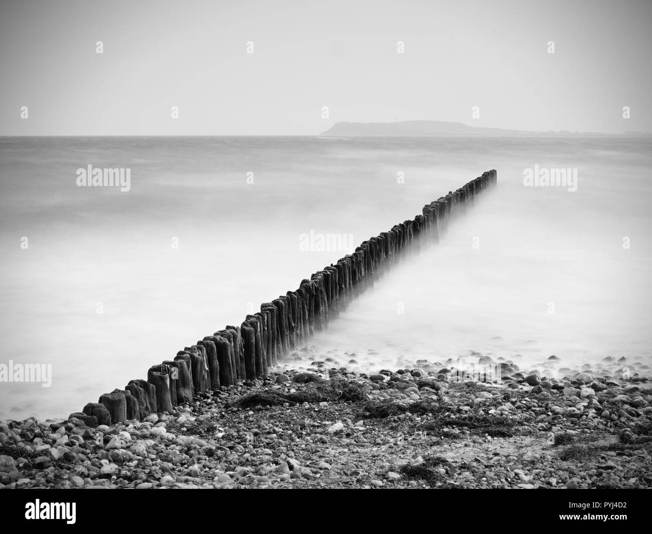 Baltic Sea shore in strong wind. Breakwater built of wooden logs by the Baltic Sea. Winter season - Stock Image