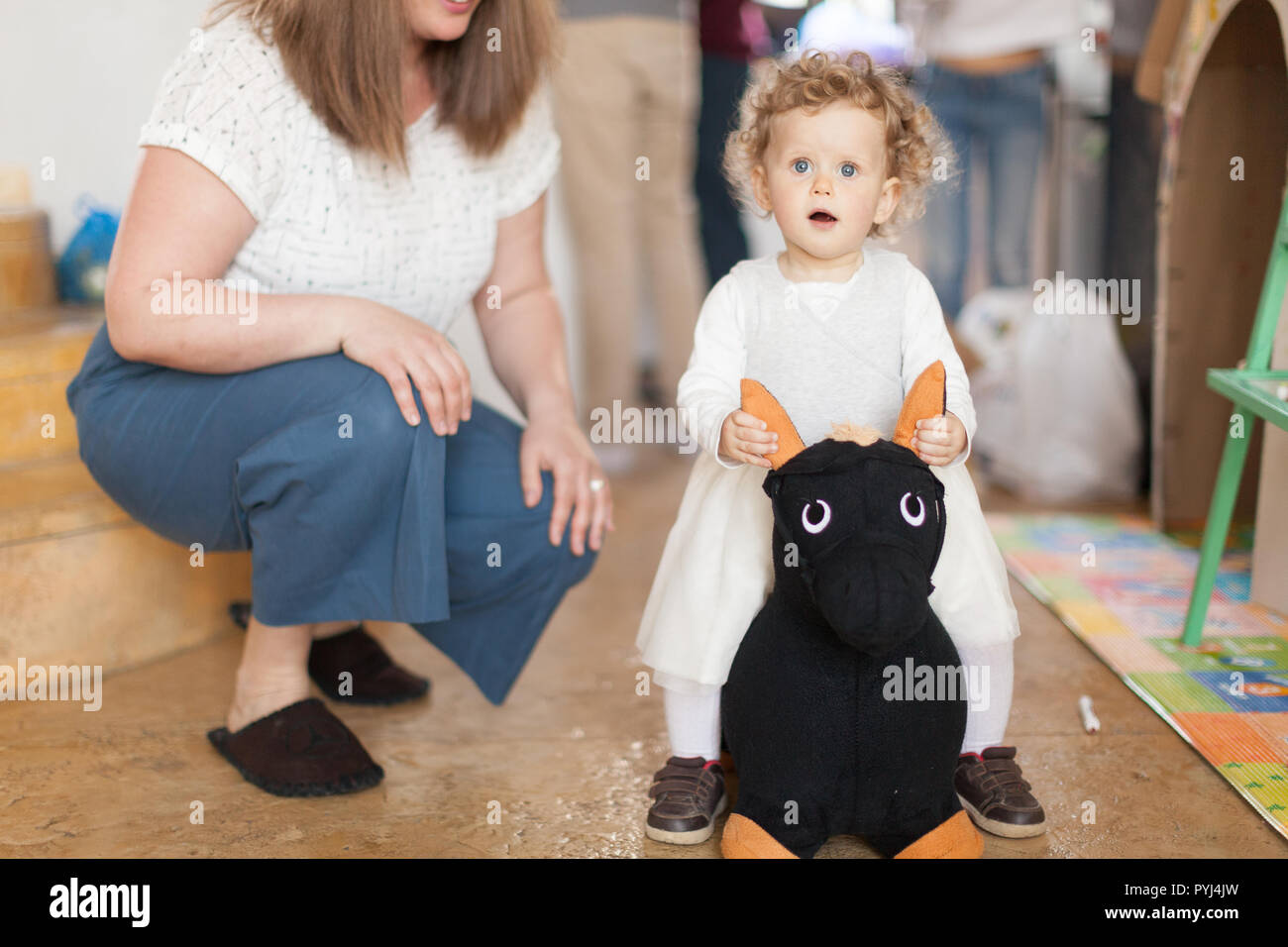 Curly little girl sitting on a black donkey toy and woman near in the white t-shitr and blue trousers sitting down at home with people in the backgrou - Stock Image