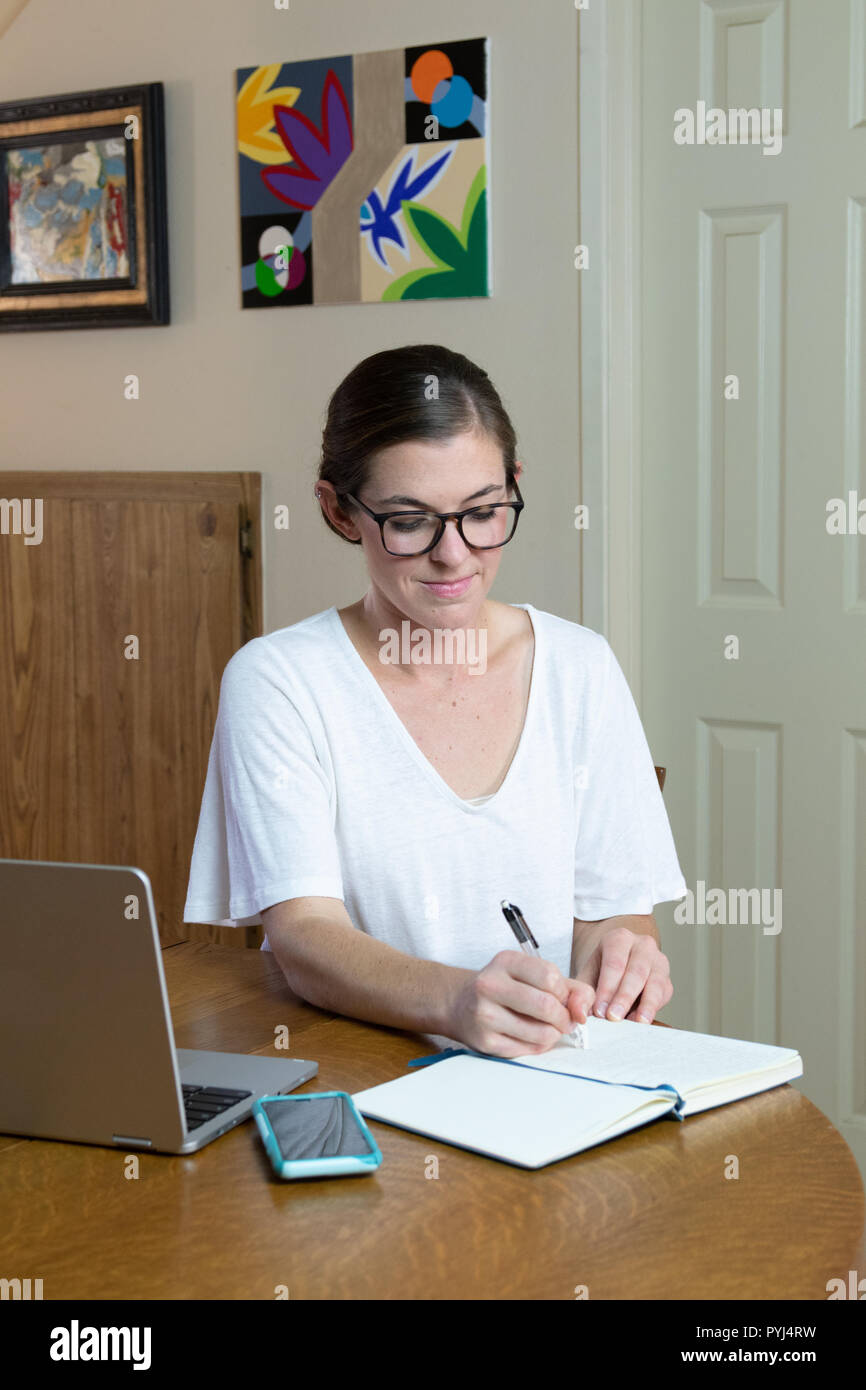 young woman artist writing in journal with cell phone and laptop to