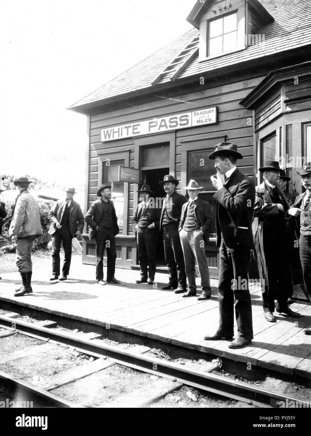 photo from 1900 of gentleman and prospectors standing at the White Pass & Yukon Railroad Station in Alaska - Stock Image