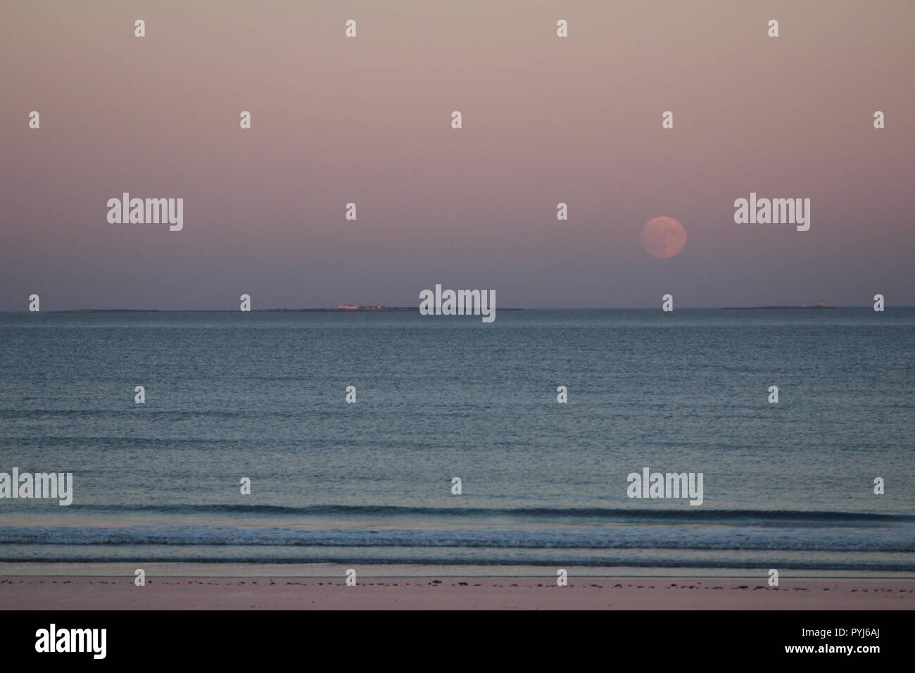 The moon rises in a purple haze floats above the ocean. - Stock Image