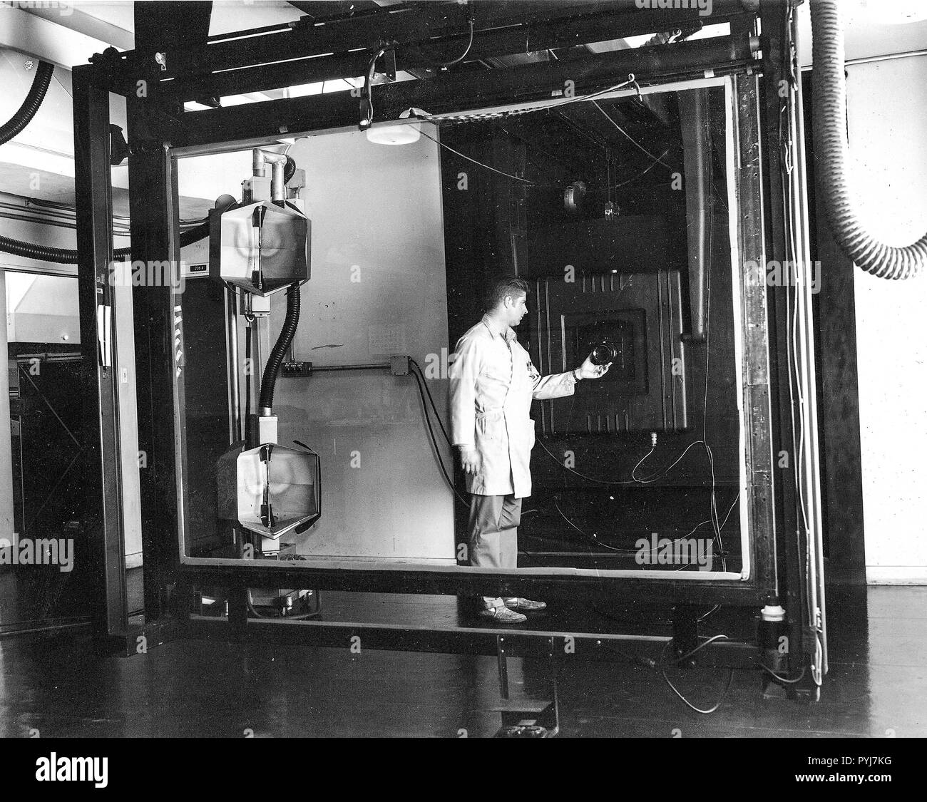 Jay Prendergast adjusts the lens on a Robertson 48-inch, 4.5 ton camera. Installed in 1959, the camera was used for precise scale transformation of mapping separates and composites. This photo was taken in Menlo Park, CA in 1965. - Stock Image