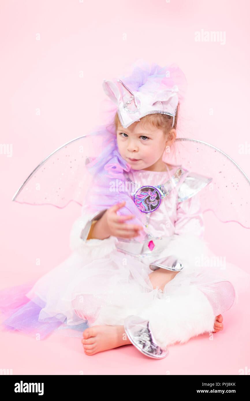 Portrait Of A Little Girl In Glitter Unicorn Costume On Pink