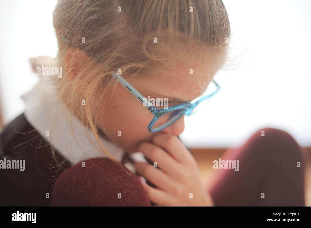 pensive little beautiful caucasian girl in glasses and school uniform think deeply - Stock Image