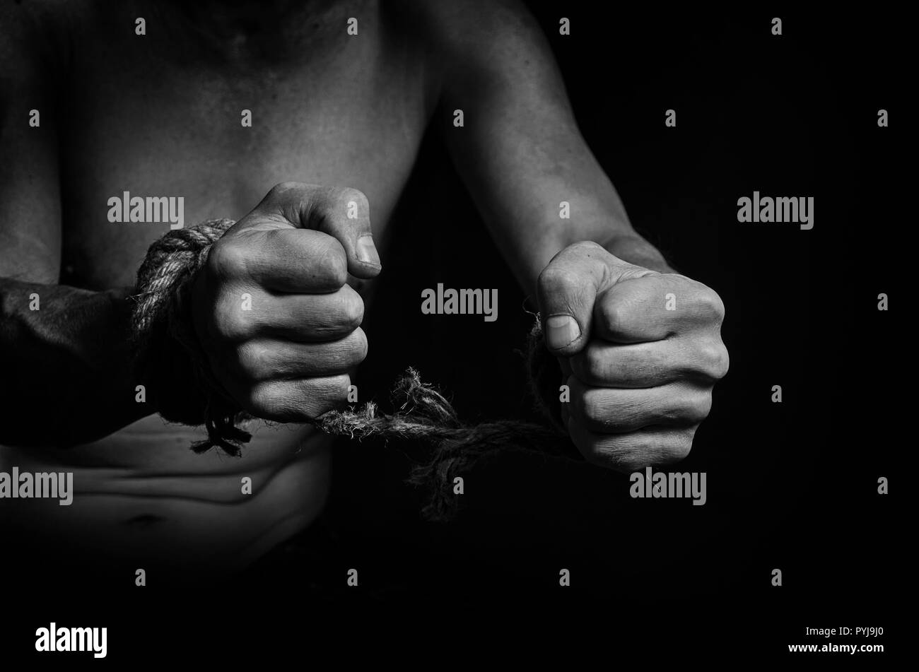 Man breaks the rope that bound his hands. - Stock Image