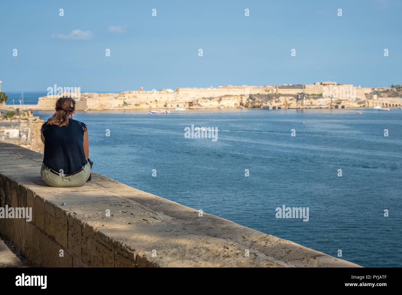 Wide angle view of a young lady sitting on the harbour wall looking looking at the view. Horizontal. Malta Grand hourbour - Stock Image