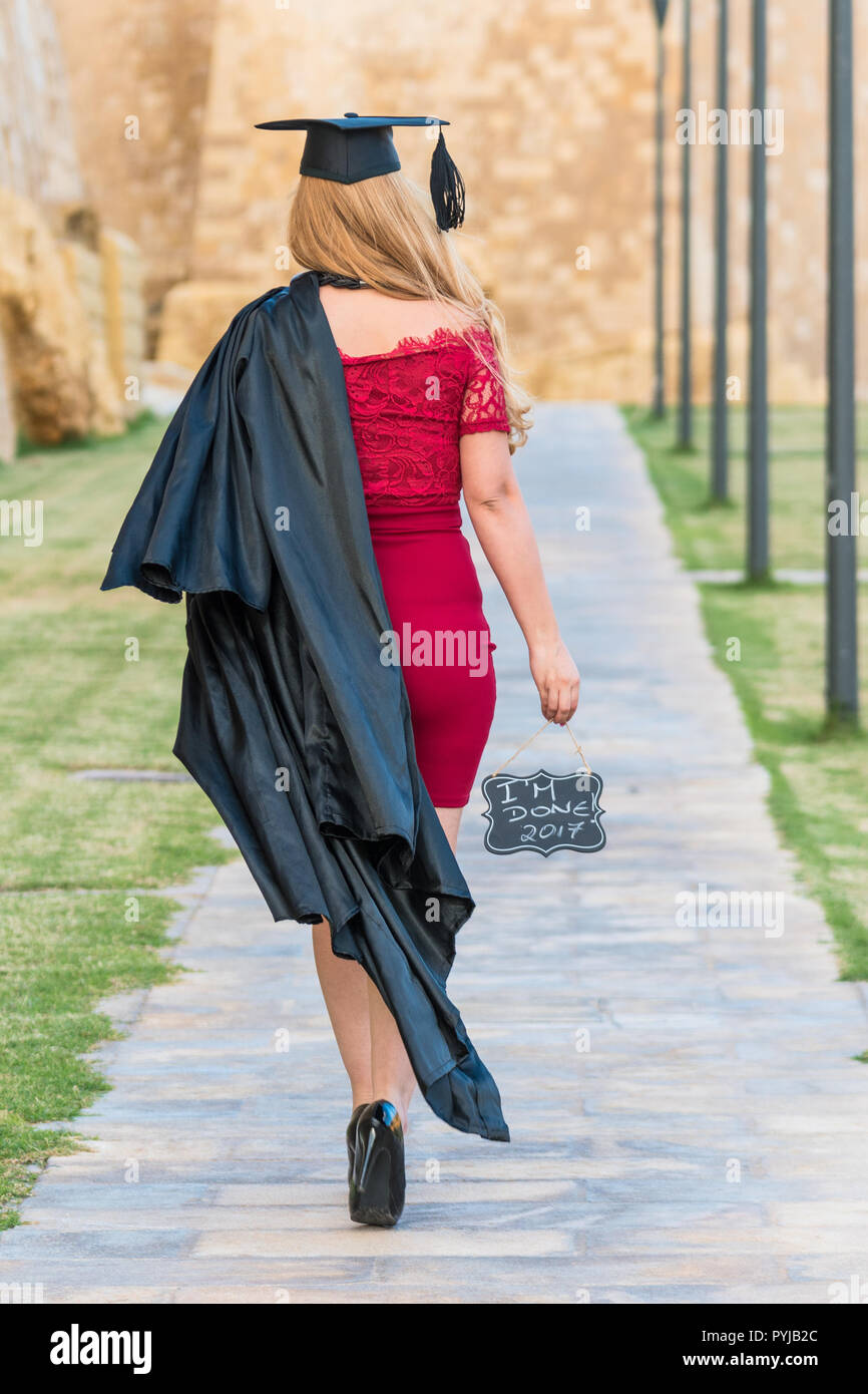 Blonde Female graduation walking away in a path holding I am done 2017 and gown in a red dress - Stock Image