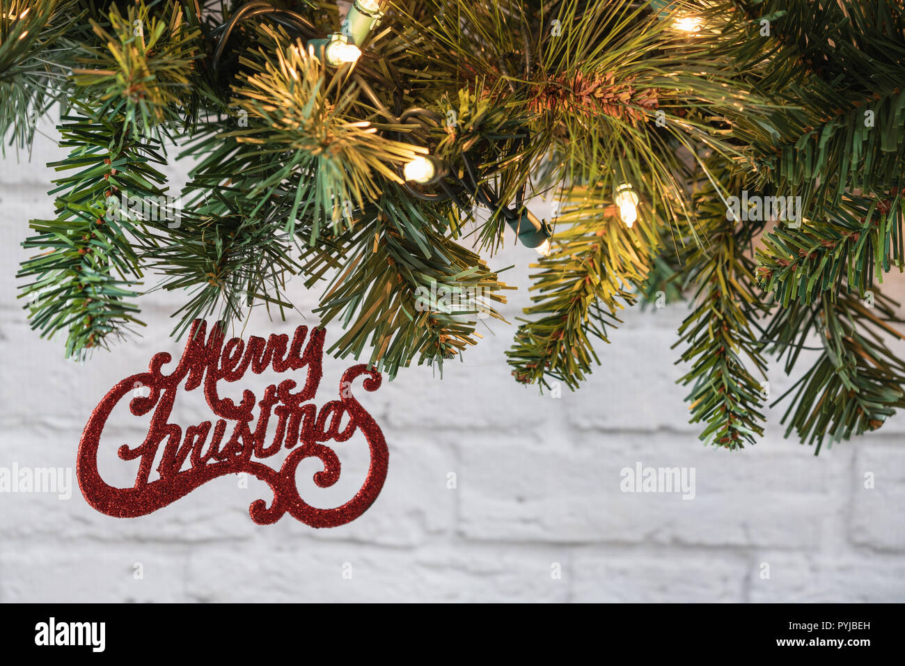 Merry Christmas Glitter Ornament Hanging From Greenery Garland In