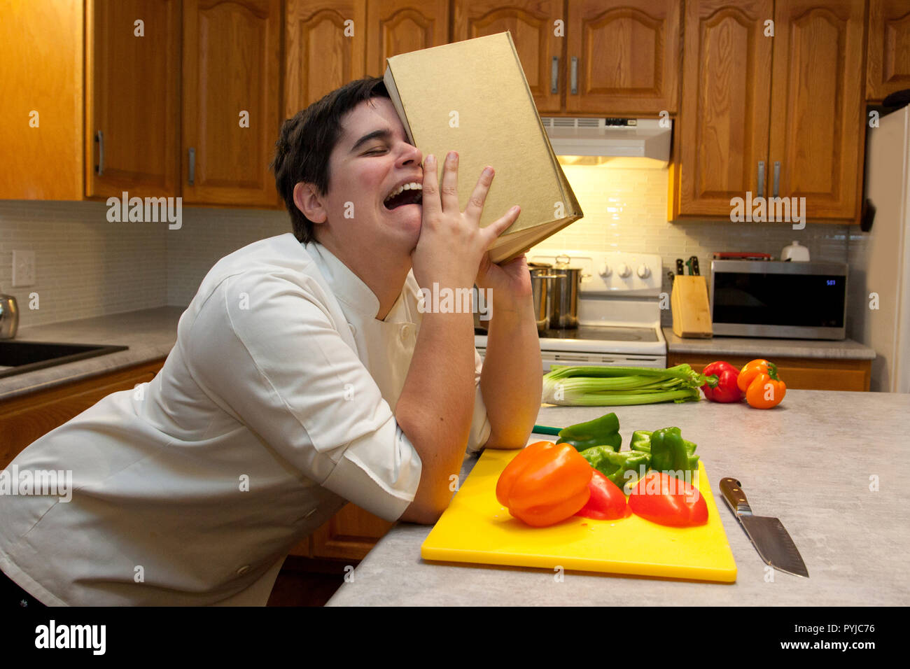 Person crying in the kitchen, sobbing into their cookbook with vegetables in the foreground - Stock Image