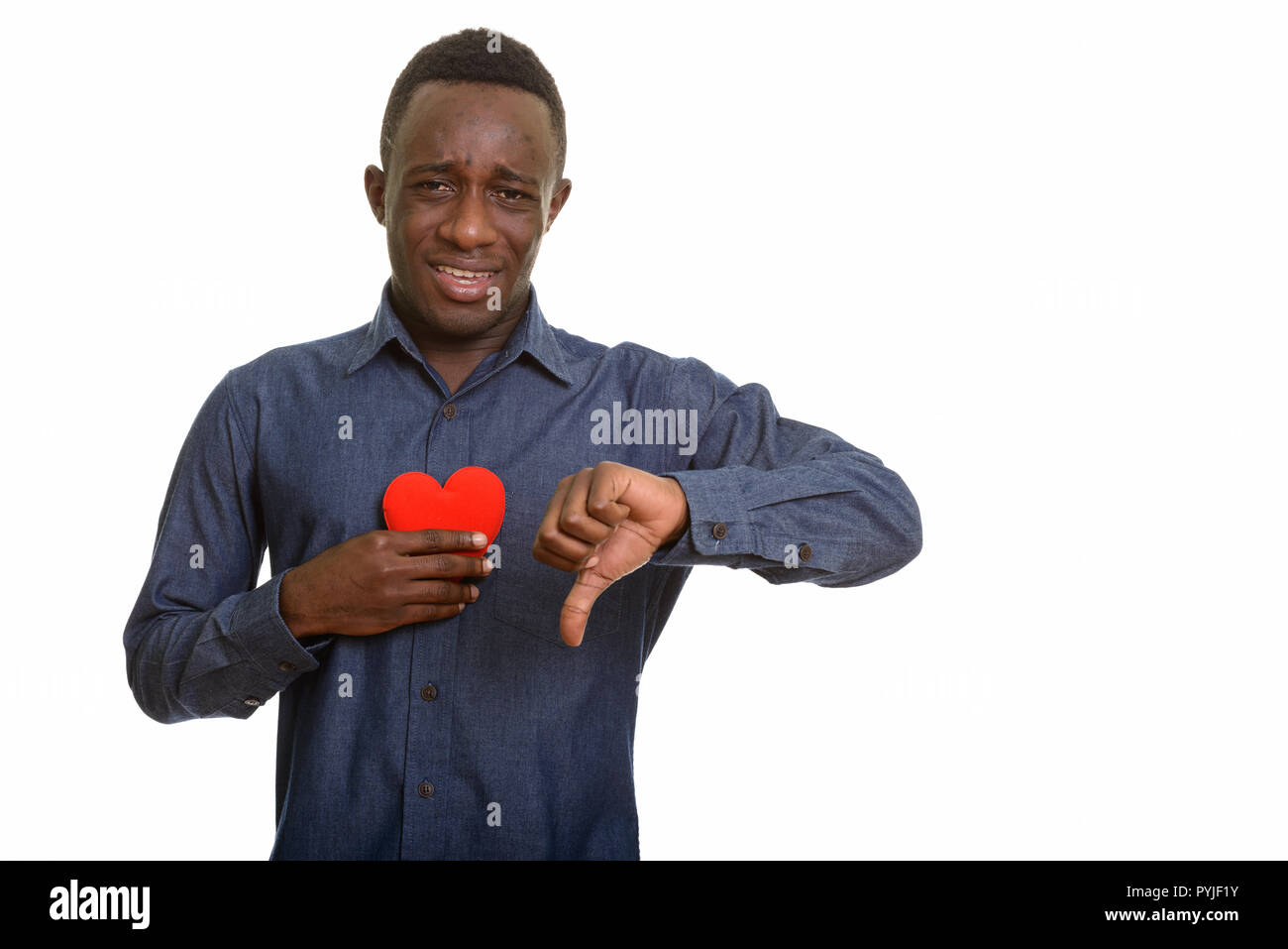 Young sad African man holding red heart on chest and giving thum Stock Photo