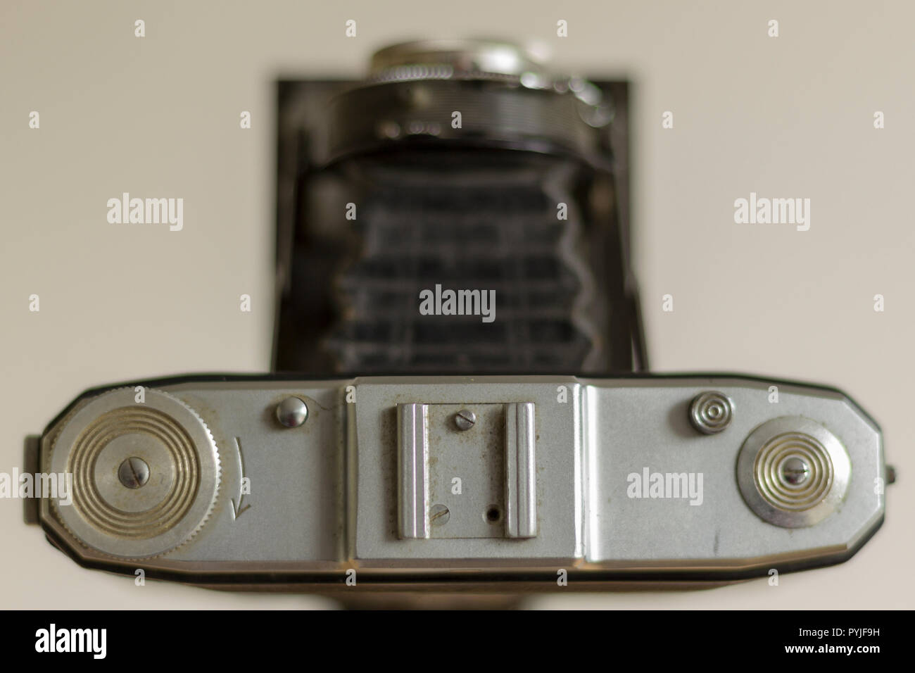 Overhead view of 120mm film camera with a folding bellows lens (out of focus) focussing on the film wind-on and shutter release buttons and flash shoe - Stock Image