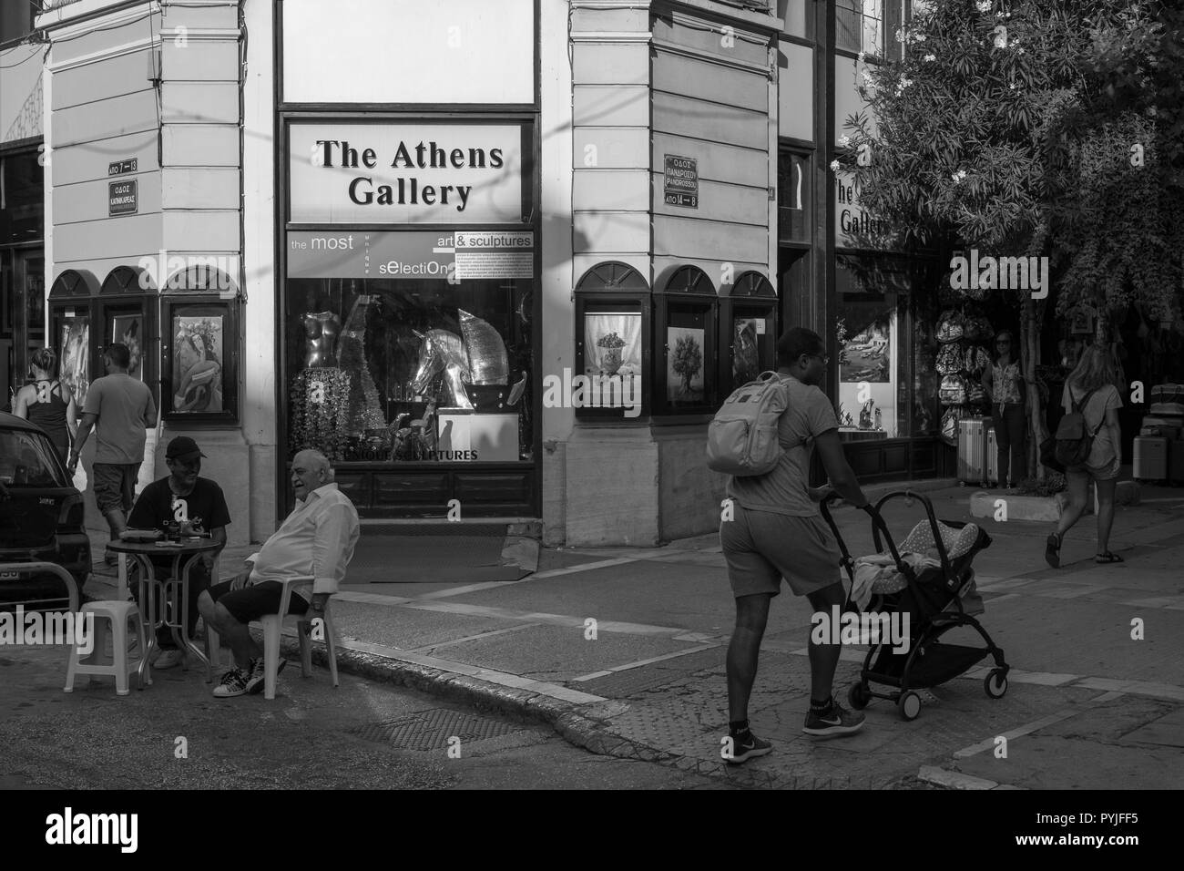 Sunday evening when shops are closed downtown Athens, people are more relaxed. - Stock Image