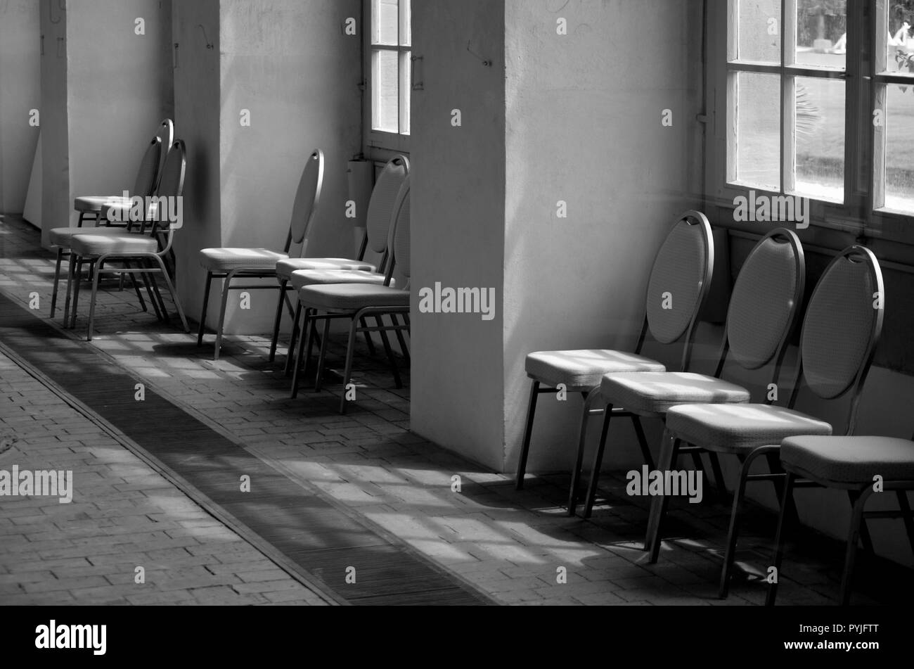 Chairs standing under windows in a large hall - monochrome image - Stock Image