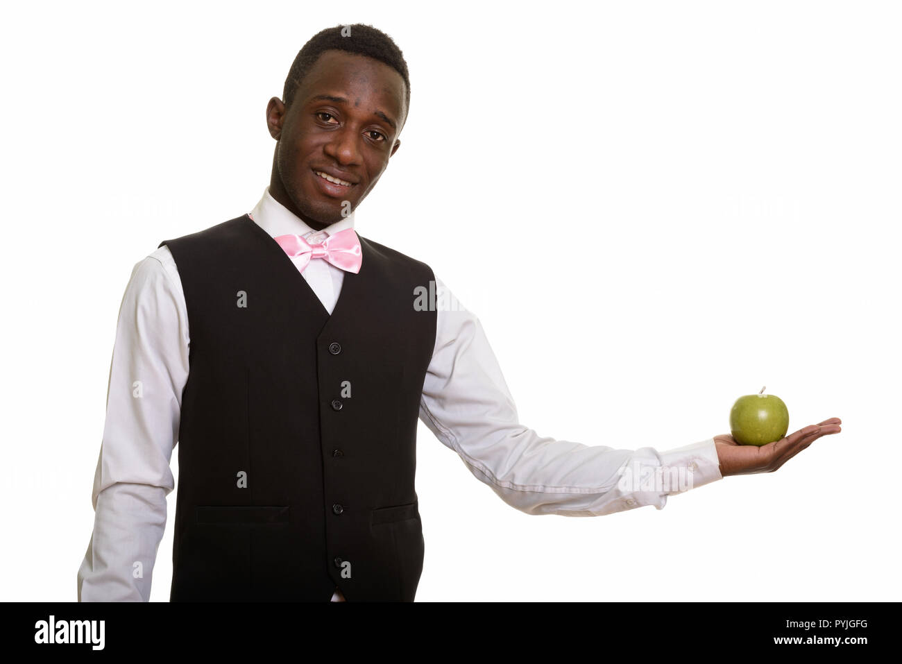 Young happy African waiter smiling and holding green apple - Stock Image