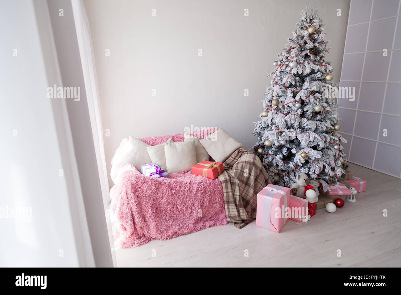 White Christmas tree in the room with gifts - Stock Image
