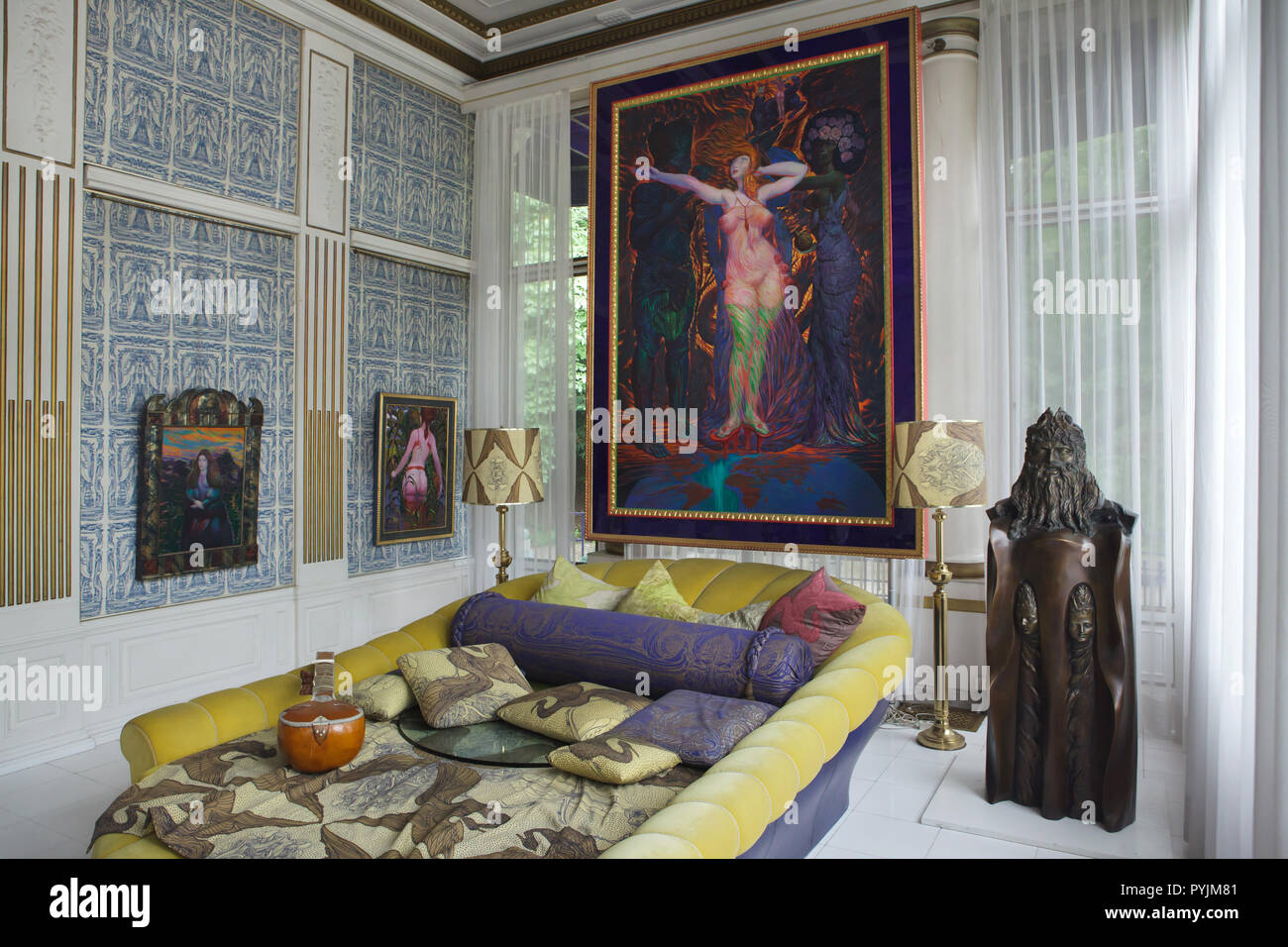 Paintings by Austrian artist Ernst Fuchs on display in the Blue Parlor in the Ernst Fuchs Museum in Vienna, Austria. The museum is housed in the former Wagner Villa I designed by Austrian modernist architect Otto Wagner and built in 1886-1888 in Hütteldorf district. The building was acquired and rebuilt by Ernst Fuchs in the 1970s. Large painting 'The Dressing of Esther' (1988-1989) is hung over the Yellow Bed also designed by Ernst Fuchs. - Stock Image