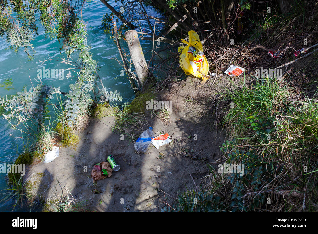 Household Rubbish dumped beside a River. - Stock Image