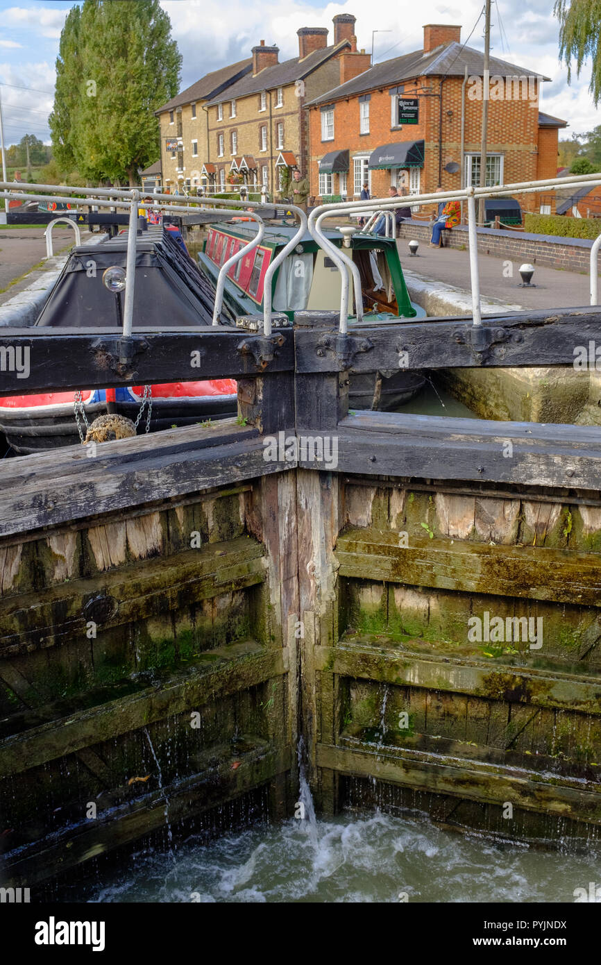 Two narrow boats at lock on Grand Union Canal, near The Canal Museum at Stoke Bruerne on the Grand Union Canal, Northampton, England - Stock Image