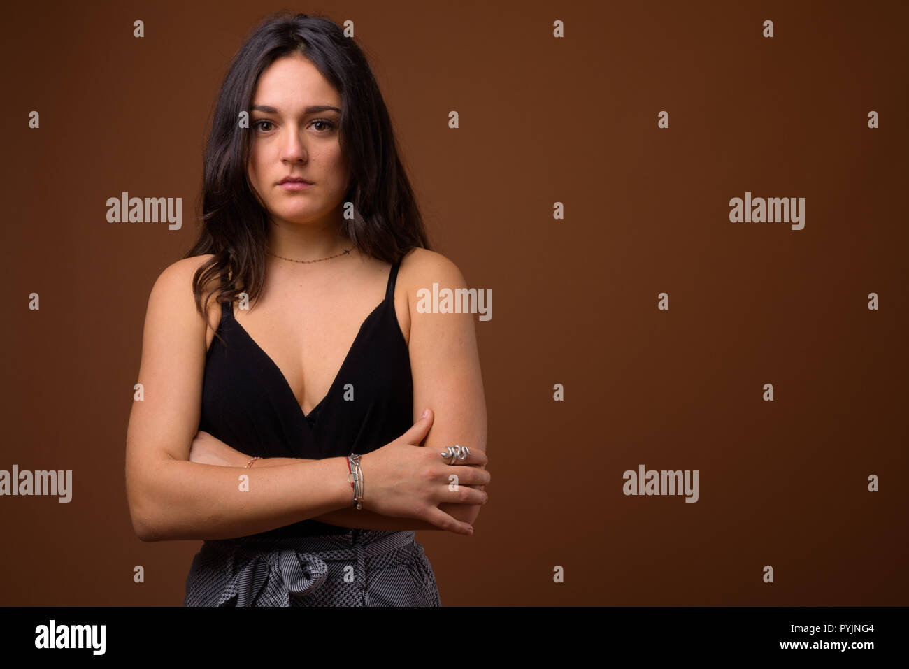 Studio shot of young beautiful woman against brown background - Stock Image