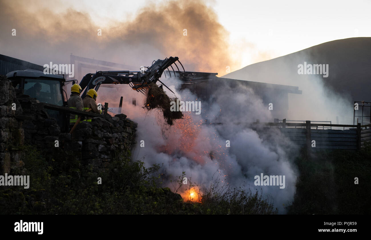 Cumbria, UK. 27th Oct 2018. Fire crew were called to a arn fire near Ravenstonedale in Cumbria at around 4pm. Hay and straw were stored in the barn, along with 50 sheep, which were all rescued by the fire service, who entered the building. Teams from Sedbergh, Kirkby Stephen and Kendal attended the incident, which was believed to have started by an electrical problem. Credit: Wayne HUTCHINSON/Alamy Live News - Stock Image
