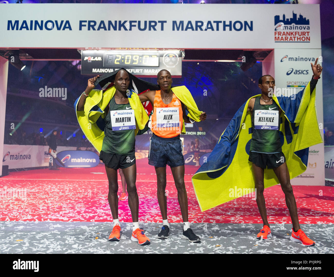 28 October 2018, Hessen, Frankfurt_Main: The winner of the Frankfurt Marathon 2018, Kelkile Gezahegn (r) from Ethiopia, the second placed Martin Kiprugut Kosgey from Kenya (l) and the third placed Alex Kibet from Kenya will finish at the Festhalle. The Frankfurt running event is the oldest city marathon in Germany. Photo: Silas Stein/dpa - Stock Image