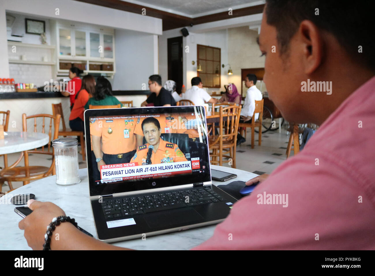 Makassar, Indonesia. 29th Oct, 2018. A resident watched the live broadcast of the fall of Lion Air JT 610 on a laptop in Makassar, Indonesia, Monday, October 29, 2018. Lion Air's flight from Jakarta to Pangkal Pinang fell in Tanjung Karawang, West Java shortly after takeoff Credit: Herwin Bahar/Alamy Live News - Stock Image