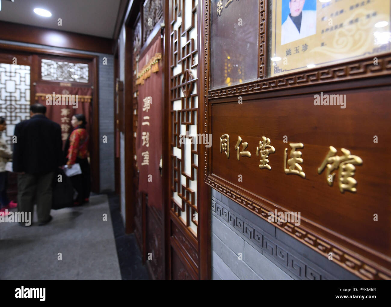 Beijing, China. 25th Oct, 2018. Citizens wait for seeing doctors at a clinic of Tongrentang, a pharmaceutical company with a history of more than 300 years, in Beijing, capital of China, Oct. 25, 2018. Established in 1669, Tongrentang is now a leading traditional Chinese medicine producer and retailer in China, and has earned a worldwide reputation. It has registered its brand in more than 100 countries and regions. Credit: Zhang Chenlin/Xinhua/Alamy Live News - Stock Image