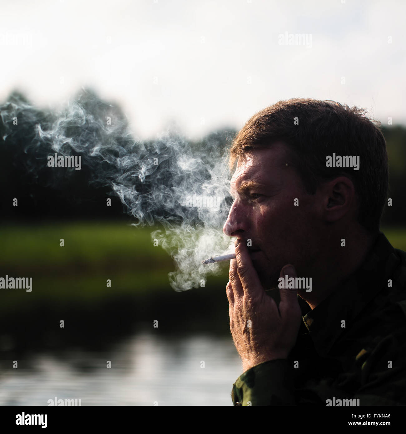 Man smoking outdoor, close-up. Smoke in the background light. - Stock Image