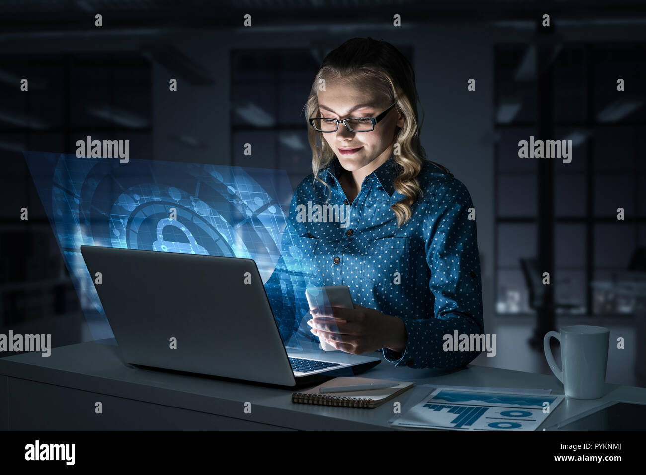 Beautiful blonde in dark office working on laptop and getting ne - Stock Image