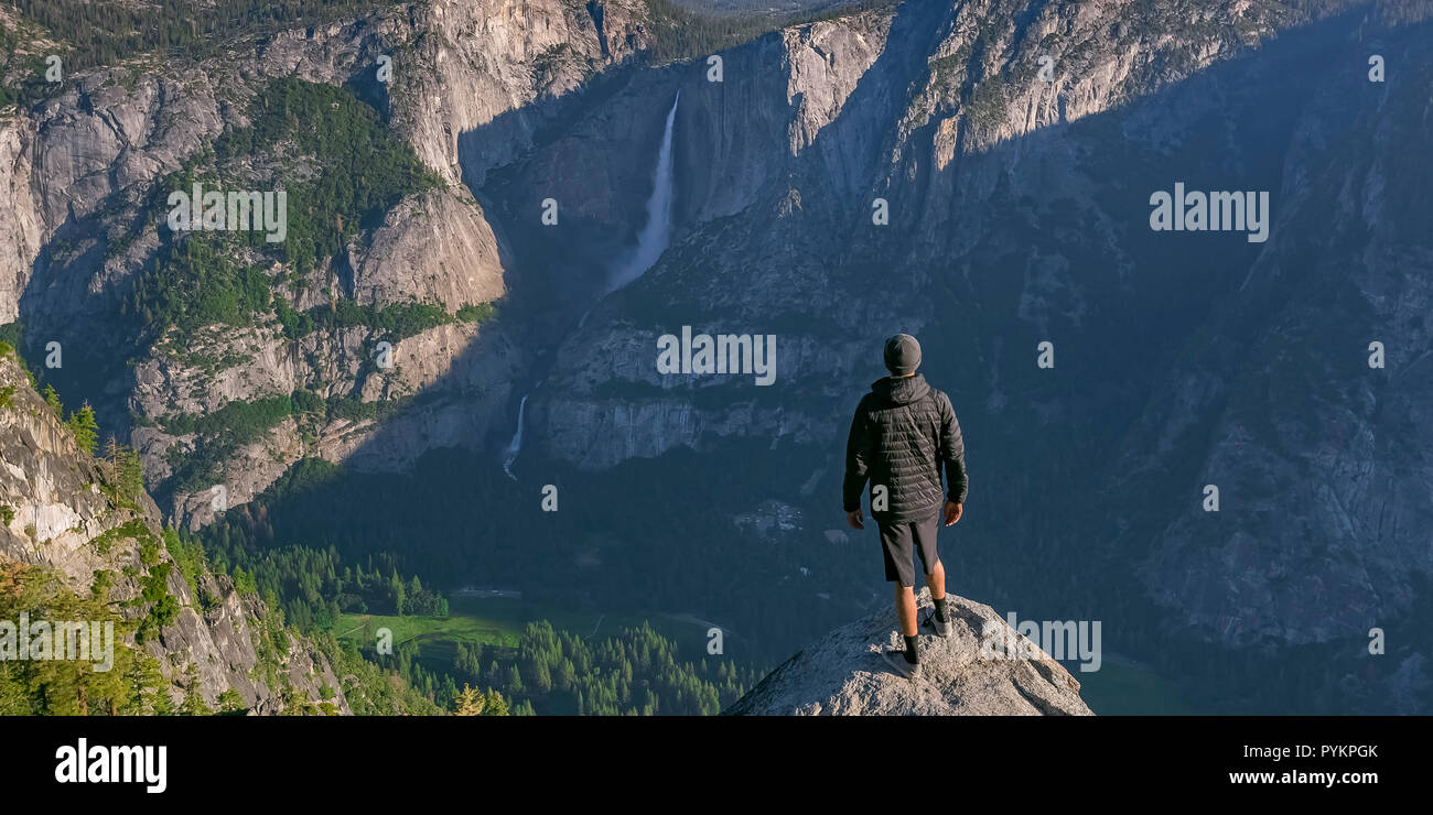 Man on cliff overlooking Yosemite Falls and valley Stock
