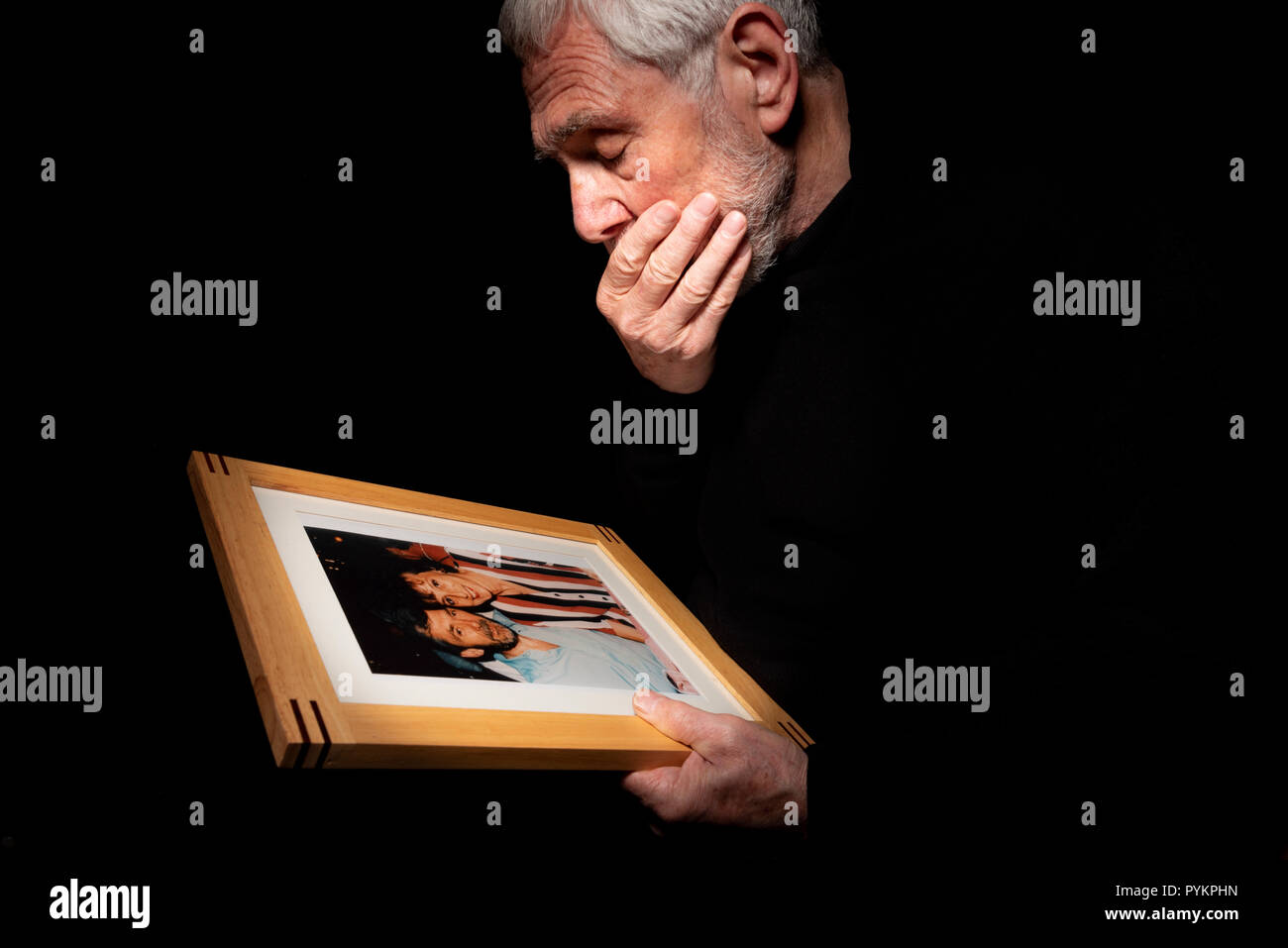 Senior grieving man. Remembering a departed loved one. Male experiencing loss and loneliness. - Stock Image