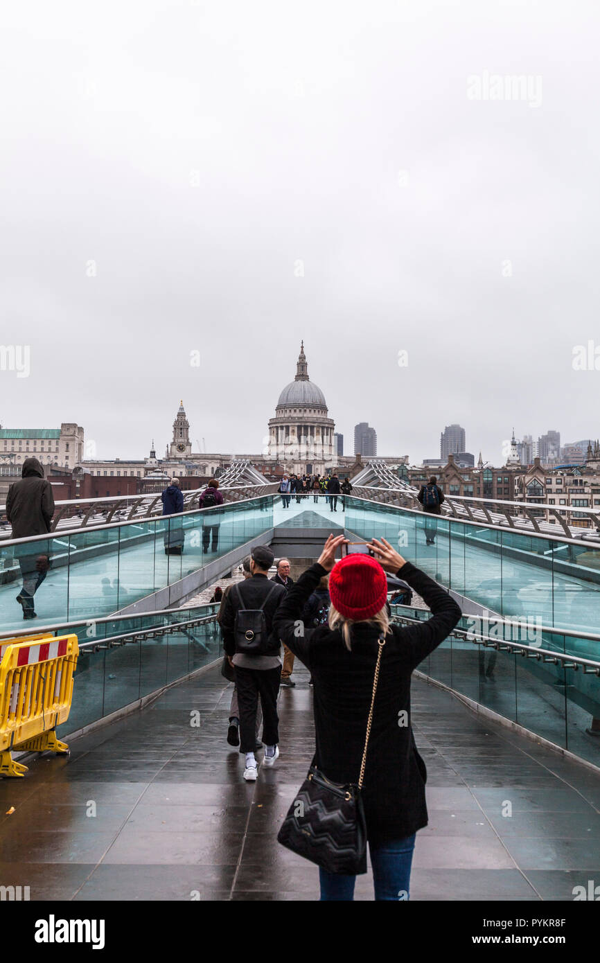 A woman in a red hat  taking a photograpgh with her phone of the the Millenium Bridge and St.Pauls Cathedral in London,England,UK - Stock Image