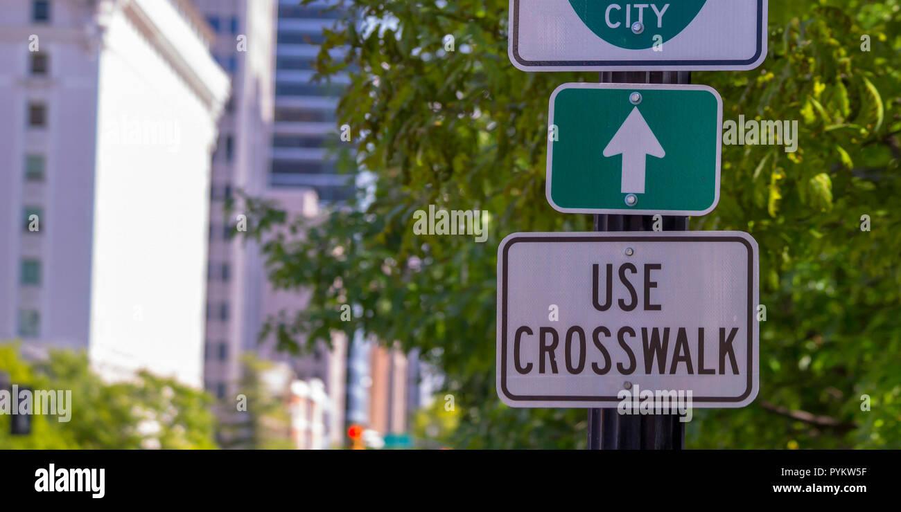 Use crosswalk and arrow signs on a sunny street Stock Photo