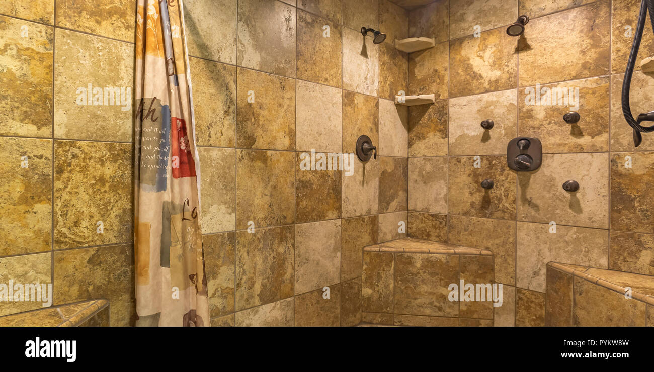 Walk in shower with brown tile wall and curtain - Stock Image