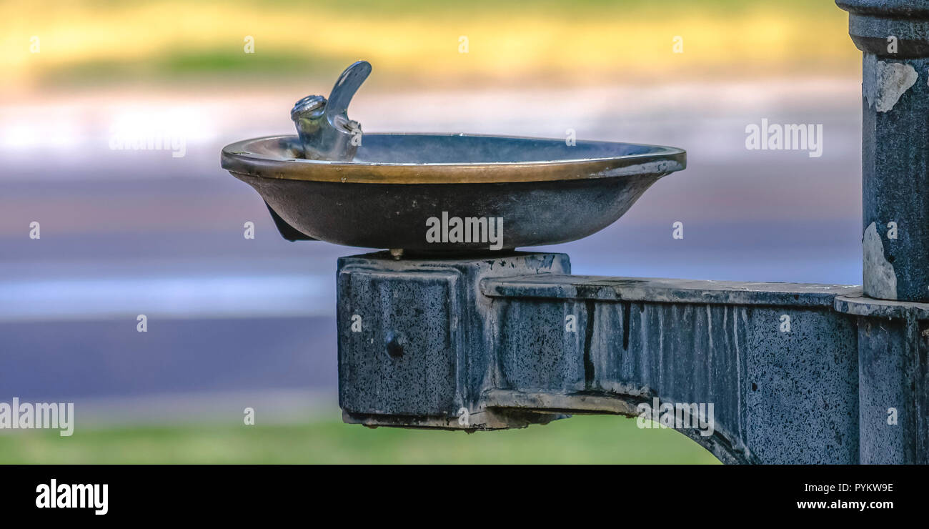 Weathered outdoor drinking fountain in a park - Stock Image