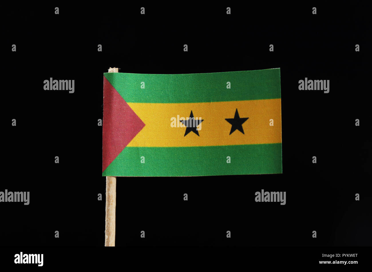 A official flag of Sao Tomé and Príncipe on toothpick on black background. Sao Tomé and Príncipe is located in central africa on island - Stock Image