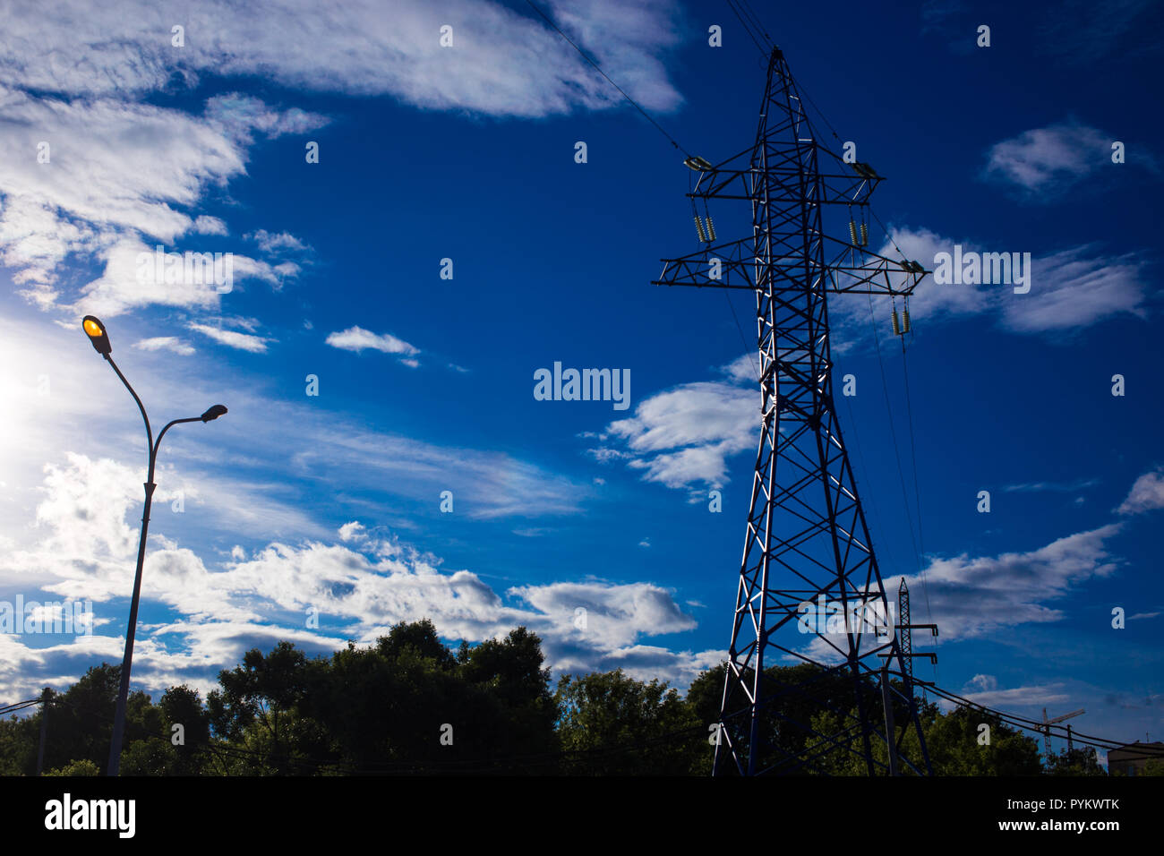 bottom view of the tower of power grids on blue sky background, High voltage, Electricity concept Stock Photo