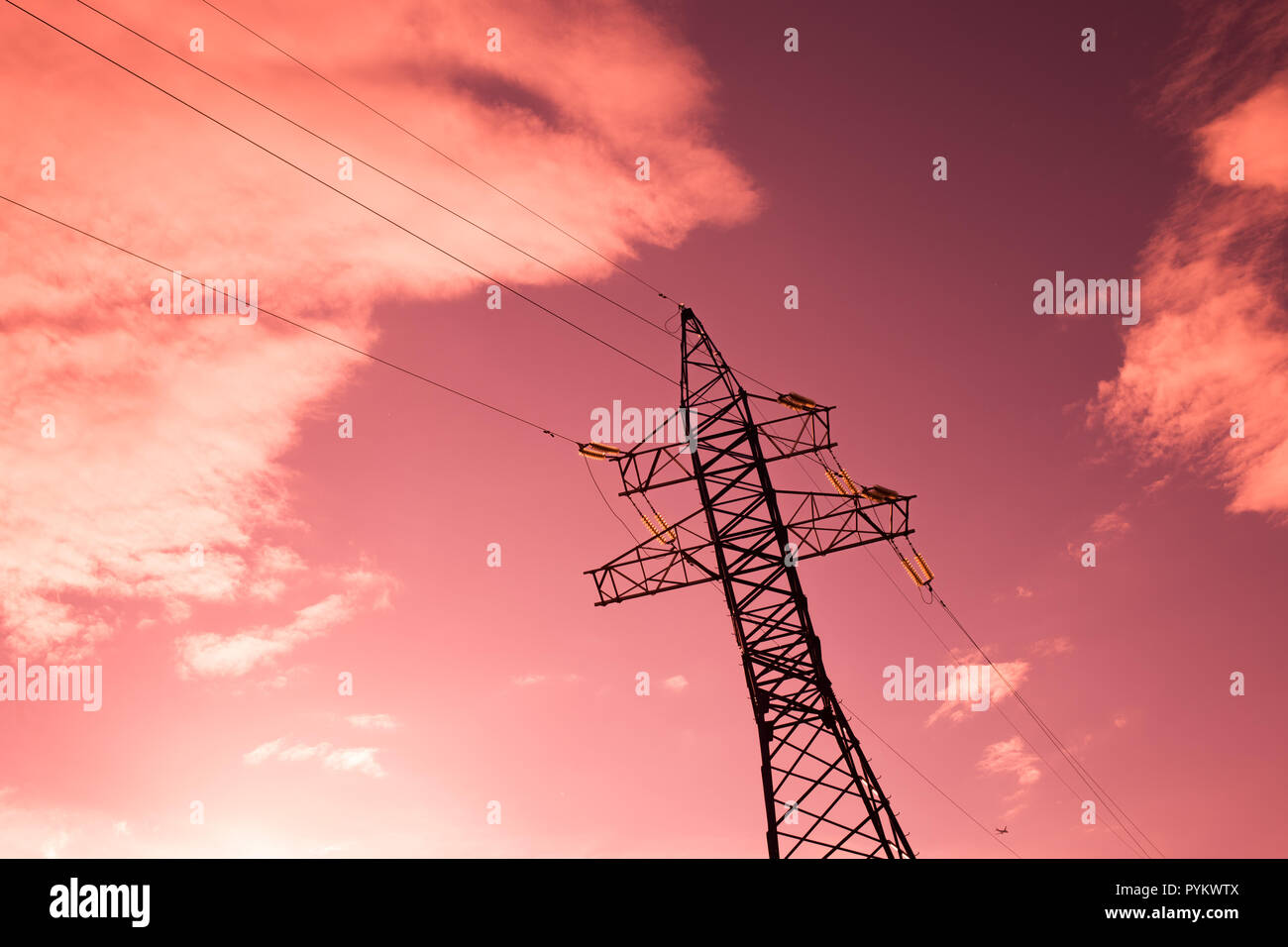 bottom view of the tower of power grids on pink sky background, High voltage, Electricity concept - Stock Image