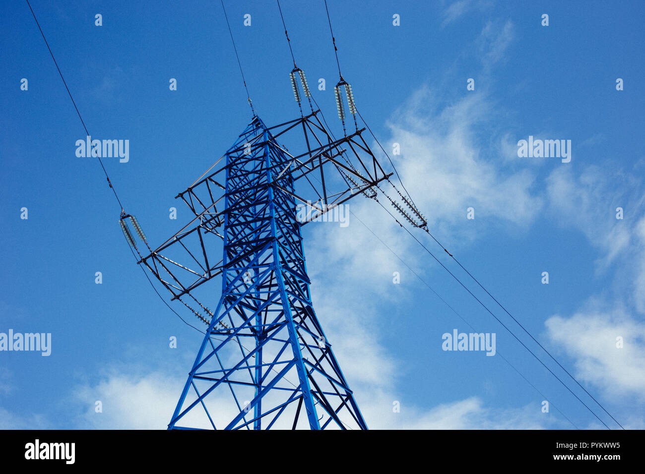 bottom view of the tower of power grids on blue sky background, High voltage, Electricity concept - Stock Image