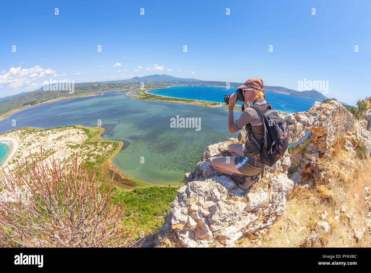 Travel female takes shots of scenic Voidokilia Beach from Navarino Castle ruin in Pylos, Peloponnese, Greece after hiking.Hiker woman photographing a popular greek landmarks. Fish eye view - Stock Image