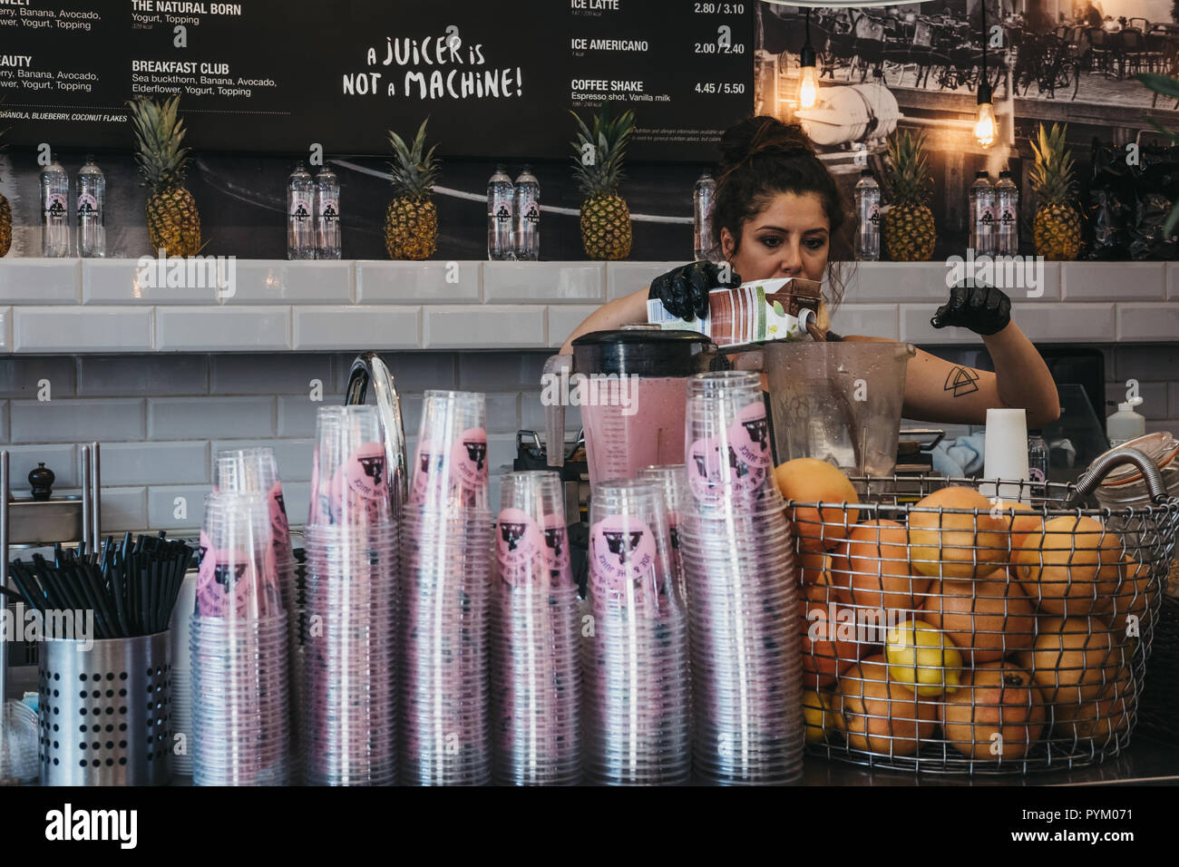 Employee making juice inside Joe & The Juice cafe in Richmond, London. Joe & The Juice is a chain of juice bars and coffee shops. - Stock Image