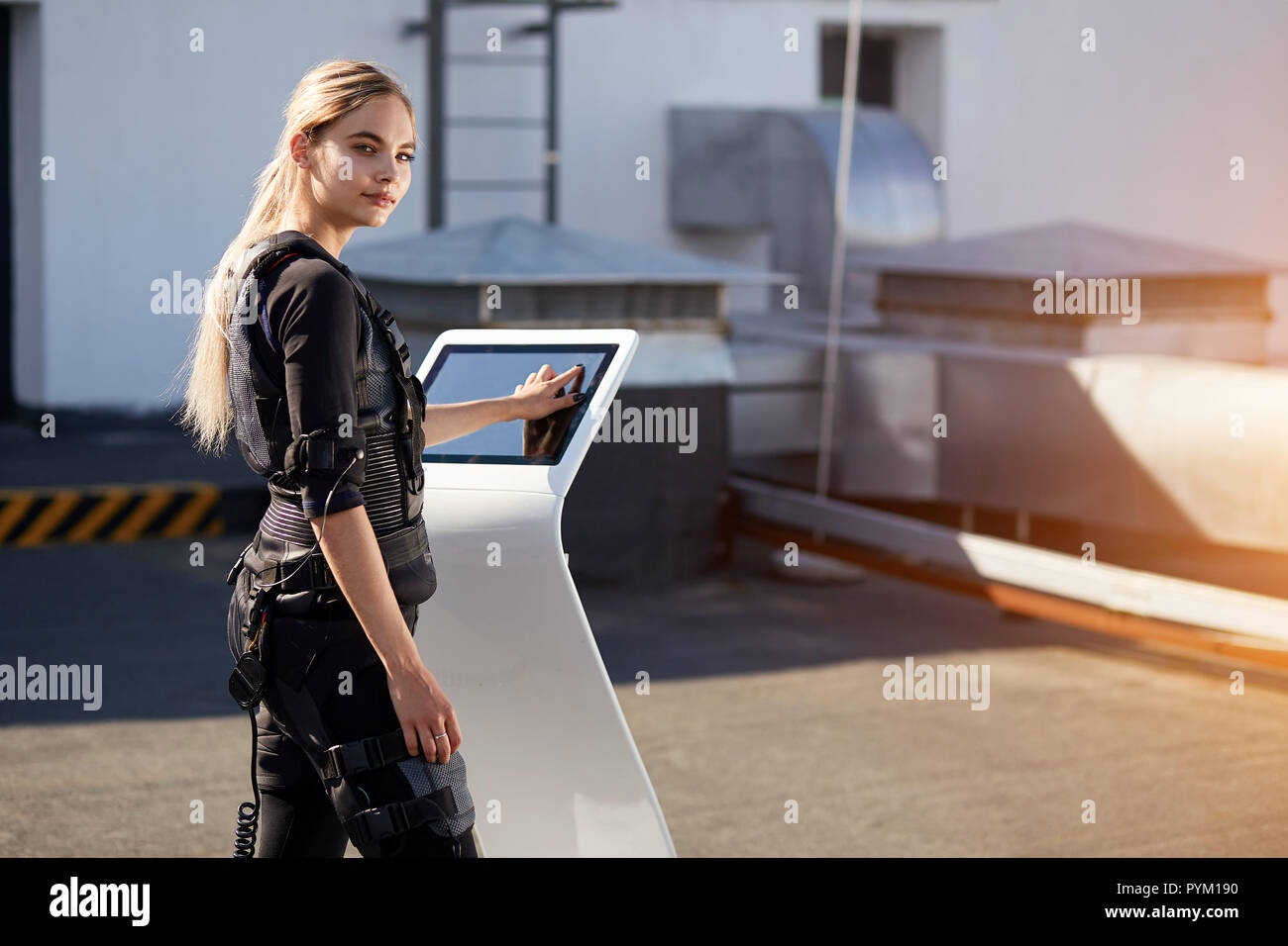 Back view photo of pleasant woman pushing on screen on EMS machine - Stock Image