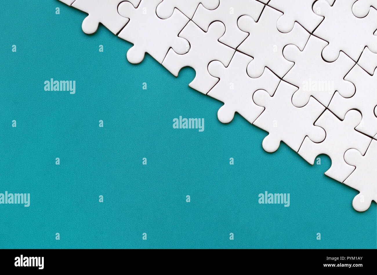 Fragment of a folded white jigsaw puzzle on the background of a blue plastic surface. Texture photo with copy space for text - Stock Image