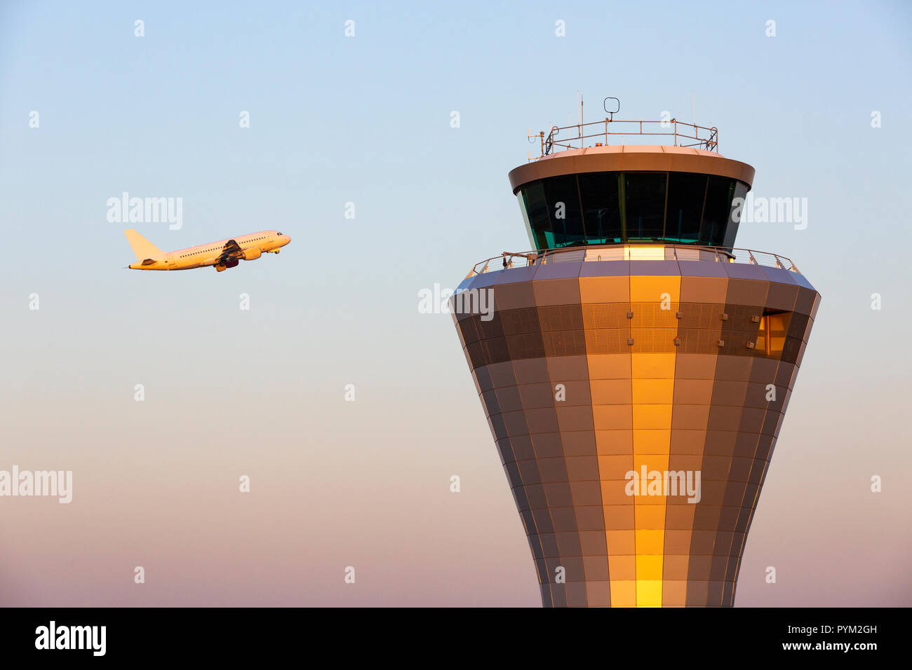 A jet aircraft flying past an air traffic control tower as it takes of at Birmingham Airport in England, UK - Stock Image