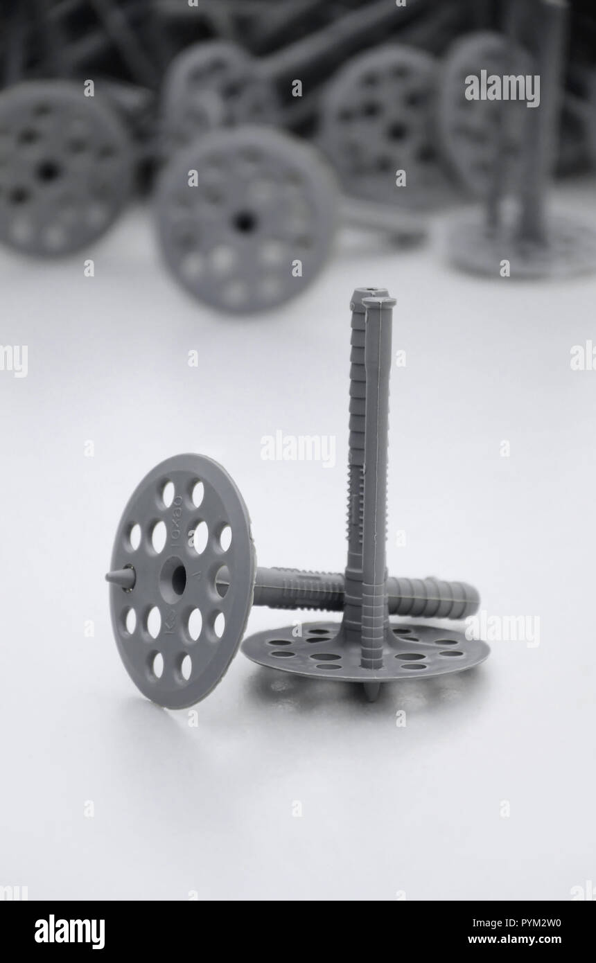 A gray plastic dowel fastening for thermal insulation with round umbrella caps lies on a gray foam polystyrene plate - Stock Image