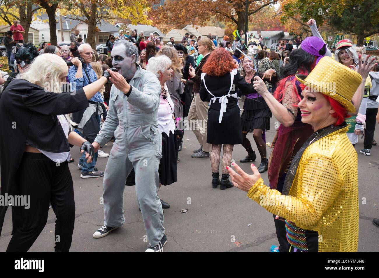 People dressed in costume for halloween dancing at the Thrill the World event in Eugene, OR, USA. - Stock Image