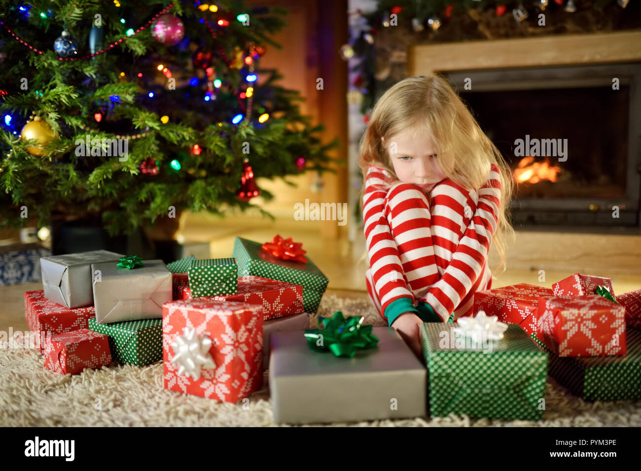 Cute little girl feeling unhappy with her Christmas gifts. Child ...