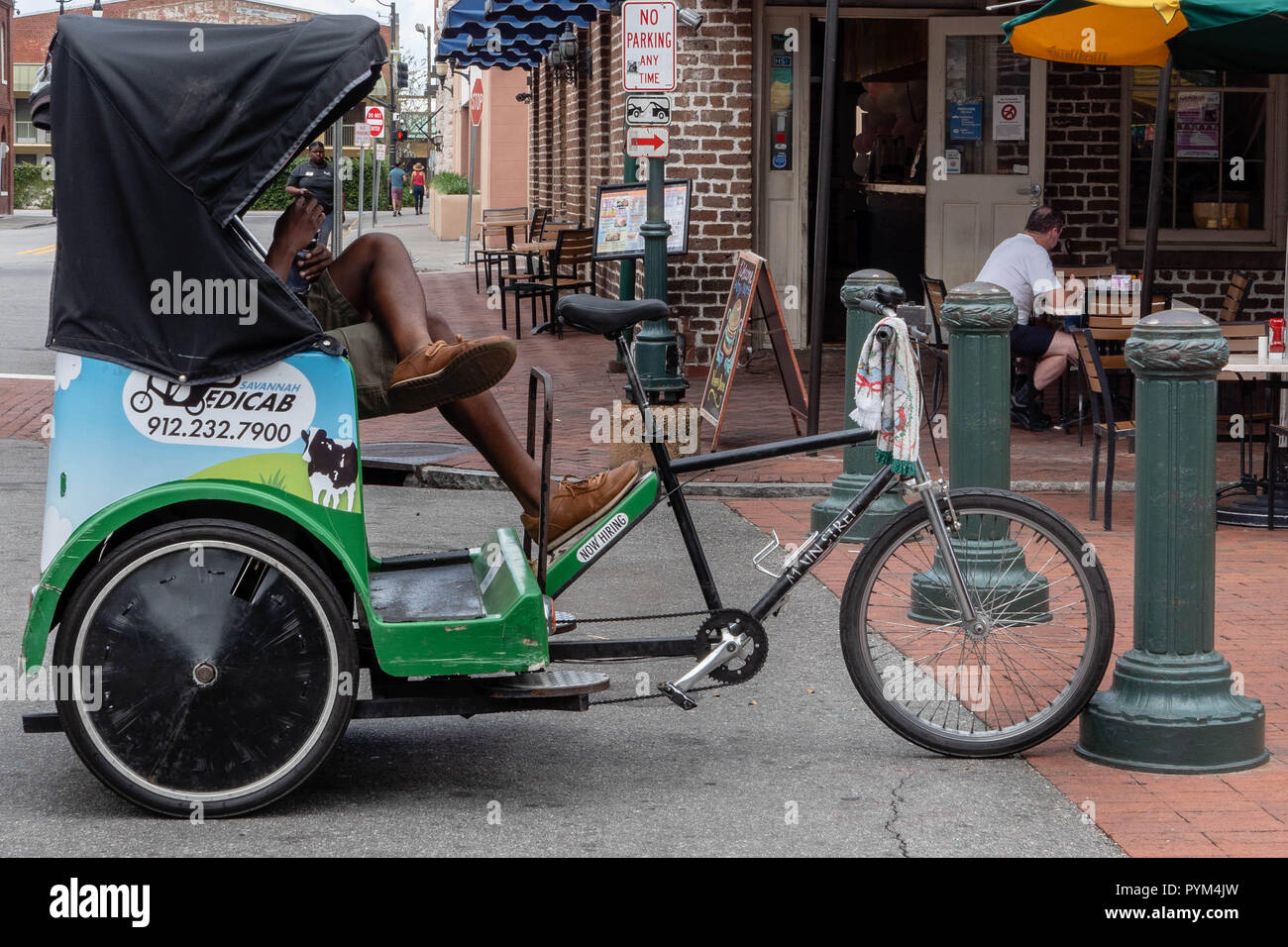 The rider of a rickshaw cycle or pedicab taxi taking a break on a street corner in Savannah Georgia USA - Stock Image