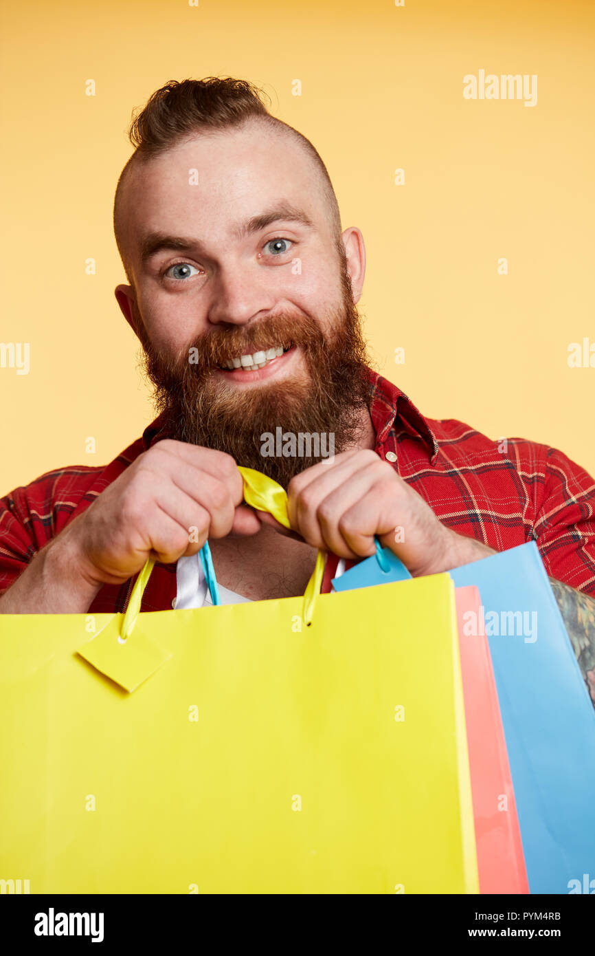 Bearded man, long beard. Brutal caucasian with moustache holding shopping packages - Stock Image