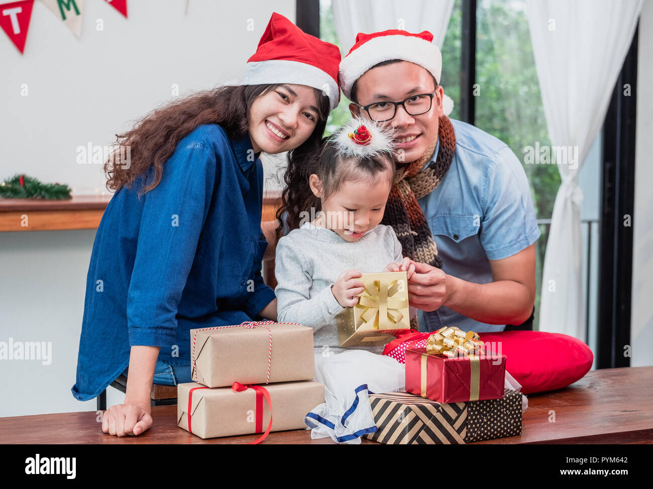 e84961ac01321 Happy family Asian family wear santa claus hat unwrap Christmas gift box at  house xmas party